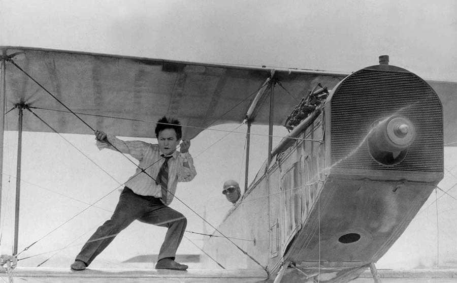 Harry Houdini on the wings of an old airplane with the wind blowing in his face from the film The Grim Game