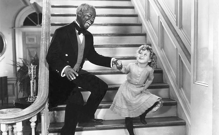 Bill 'Bojangles' Robinson and Shirley Temple dancing on the stairs in The Little Colonel