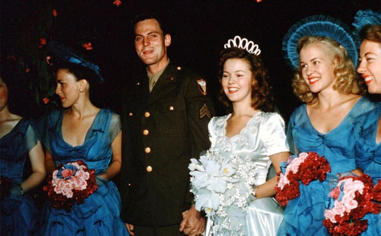 Shirley Temple and John Agar on their wedding day surrounded by bridesmaids in bright blue dresses