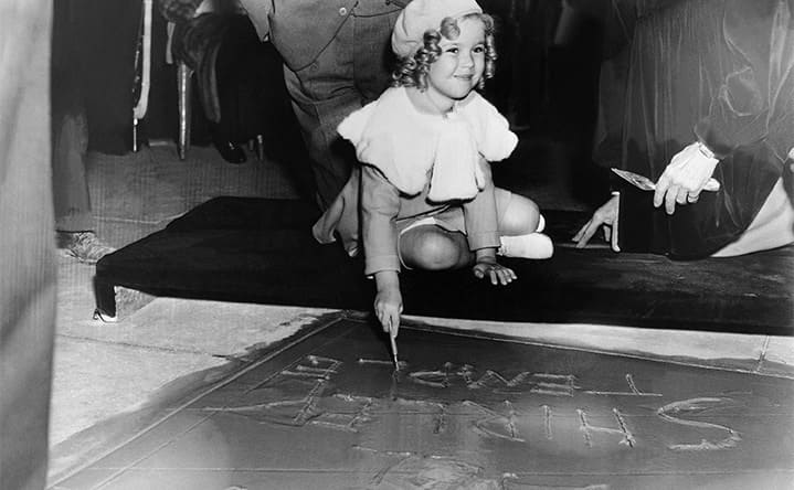 Shirley Temple signing her name in the cement outside of Grauman's Chinese Theatre