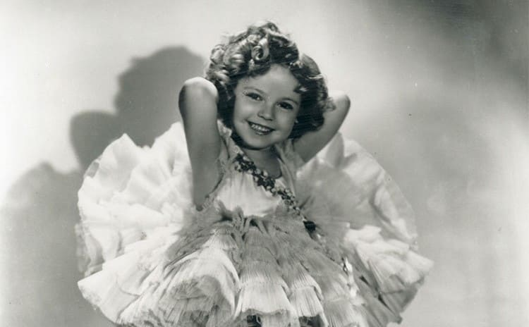 Shirley Temple as a young girl posing with a smile