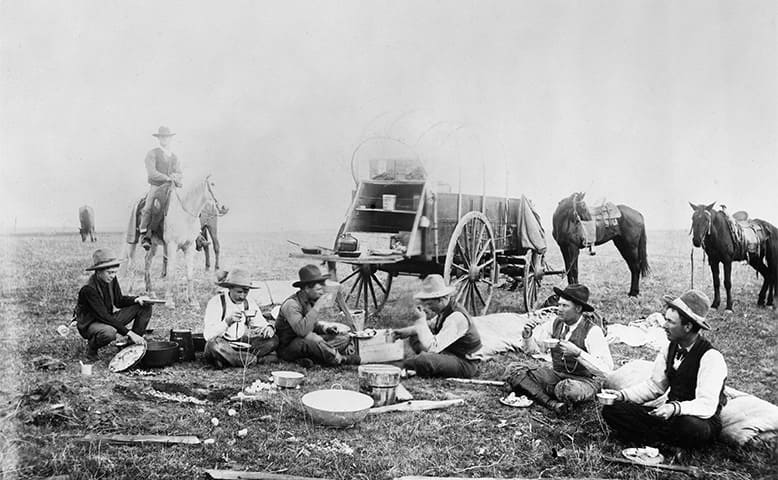 Cowboys sitting out in a hot field eating and chewing tobacco