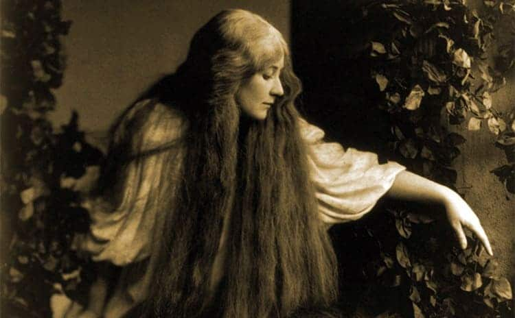 A woman with long hair sitting around ivy covering the side of a house