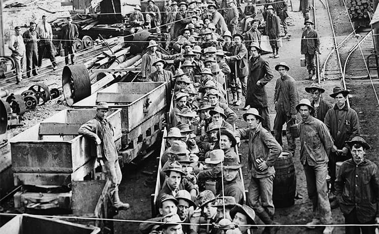 Metal miners sitting in mining cars on the way to the mines circa 1909