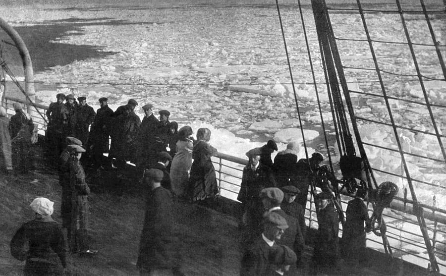Passengers on a steamship looking out over the deck into the icy water