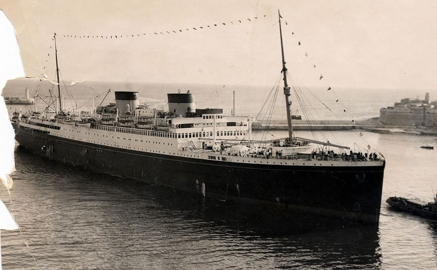A photograph of the Britannic ship in the water near a harbor