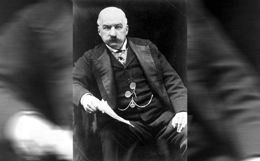 JP Morgan posing for a photograph in a full suit with pocket watches