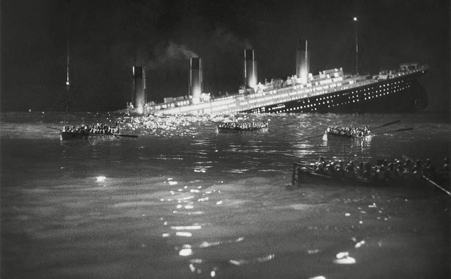 A recreation of the sinking of the Titanic with the Titanic half under the water and lifeboats in the water
