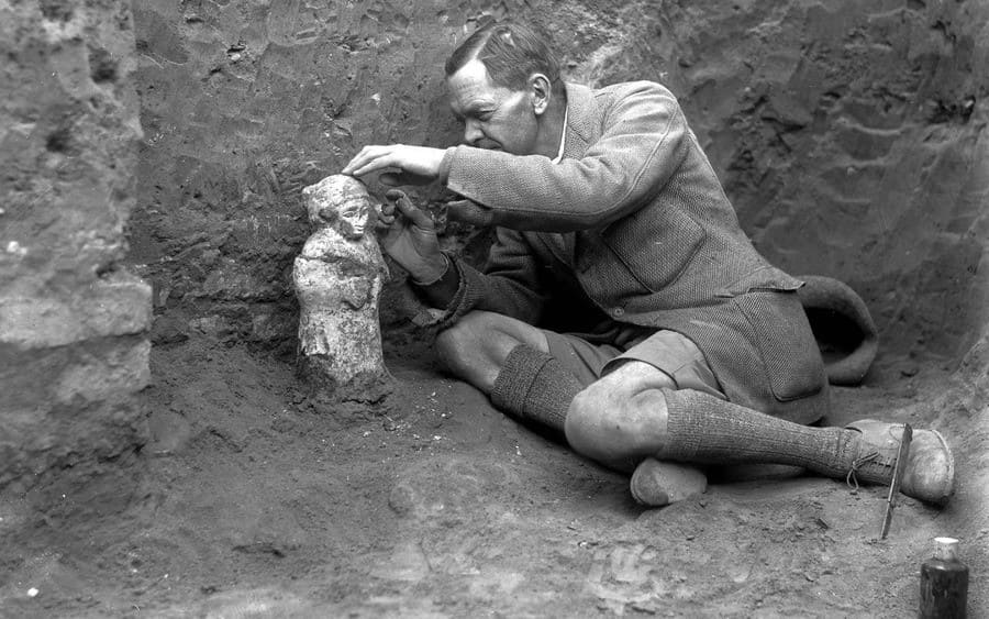 Sir Leonard Woolley carefully excavating a statuette depicting a worshipper.
