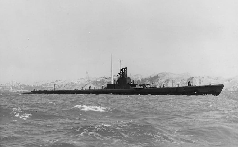 The USS Wahoo in the water with soldiers walking around the top of it