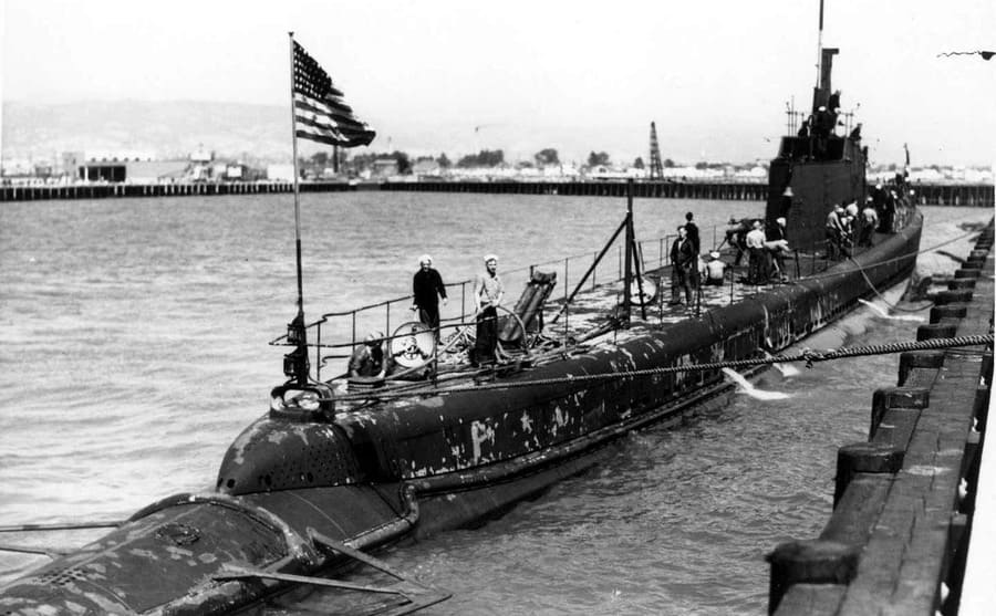 The USS Wahoo docked at Pearl Harbor with soldiers standing on the open deck