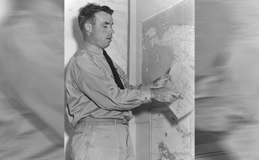 Dudley Mush Morton describing the USS Wahoo war patrol pointing at maps hung up on the walls around him and one in his hands