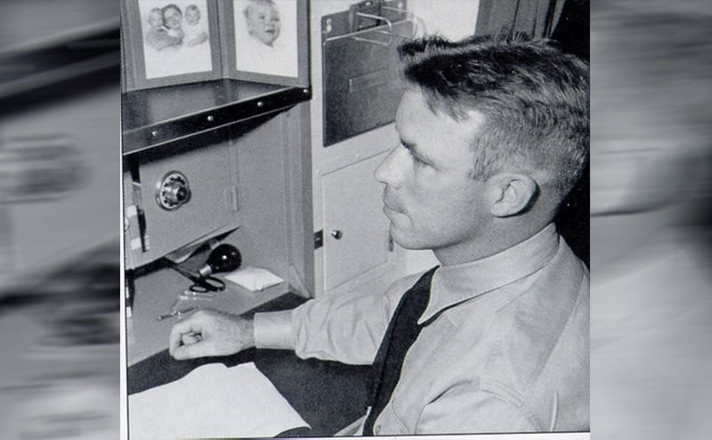 Dudley Mush Morton sitting at a desk with family photographs to his right