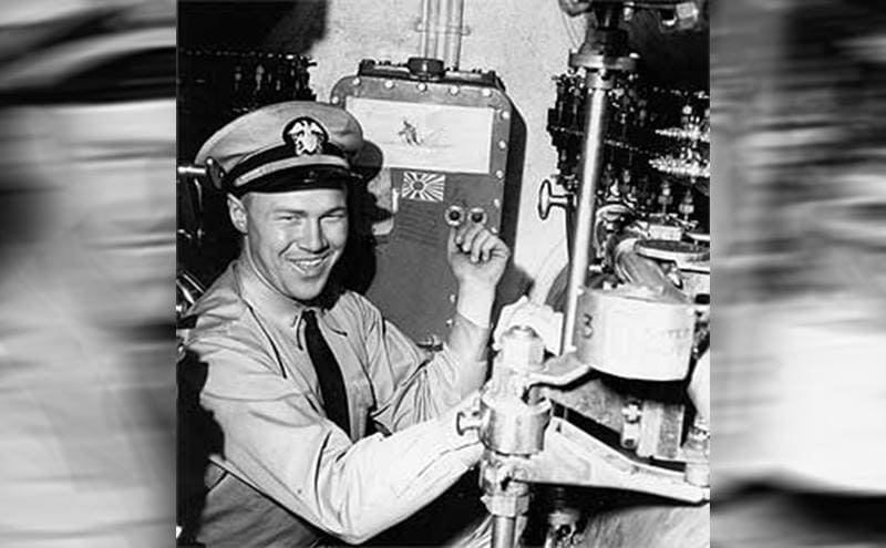 George Misch pointing to a kill flag and illustrations next to him in the forward torpedo room of the USS Wahoo