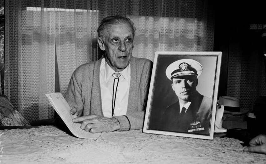 Dudley Mush Morton's father pointing to a newspaper article with a photograph of Dudley in uniform next to him on a table