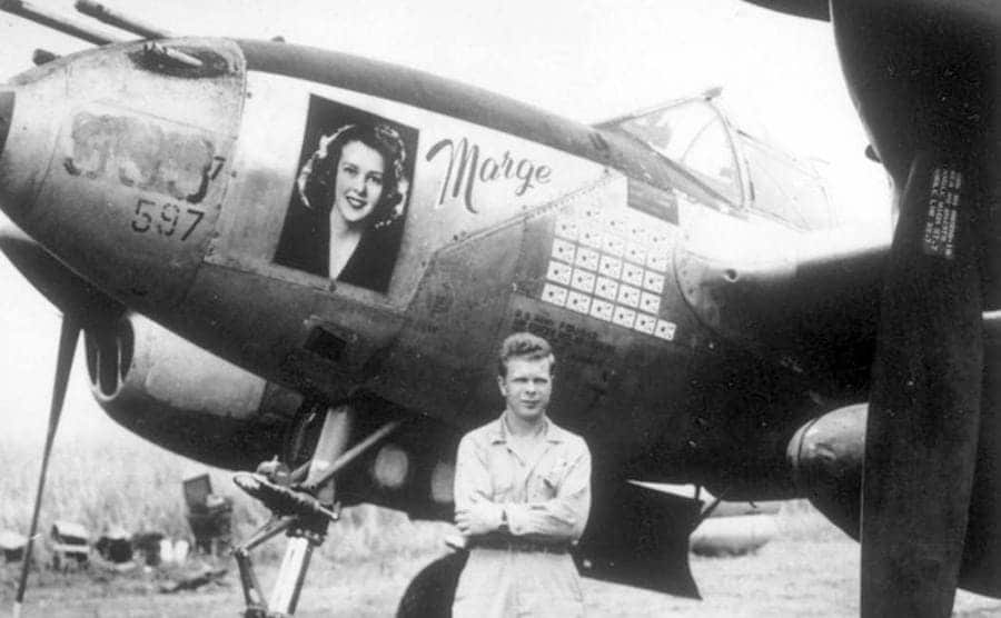 Richard Bong standing in front of his plane with a photograph of Marge on it