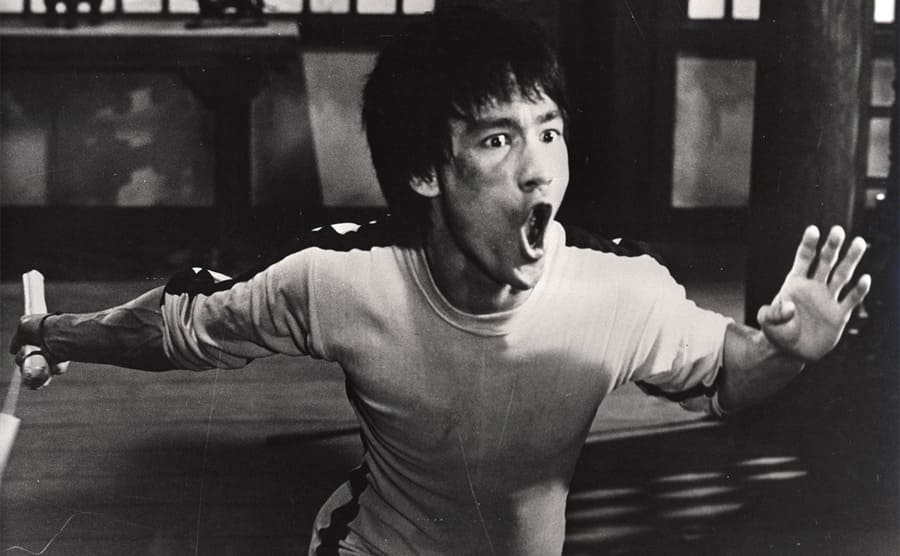 Bruce Lee lunging forward in a shot from the film Game of Death