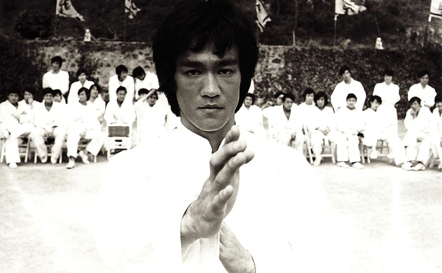 Bruce Lee in a starting position to fight in a scene from the film Enter the Dragon