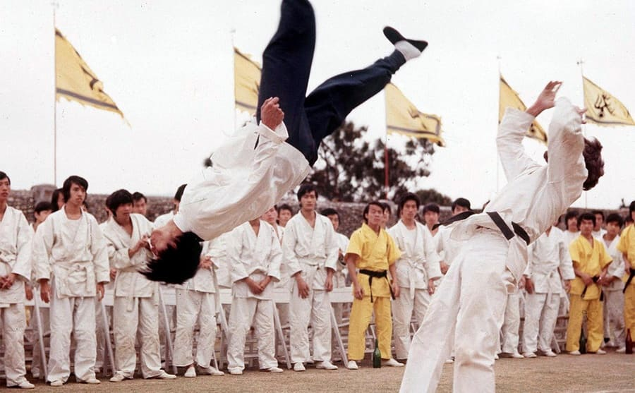 Bruce Lee doing a backflip while performing kung fu