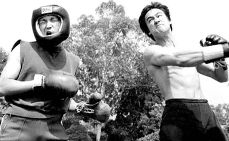 Bruce Lee with boxing gloves on sparring with another man