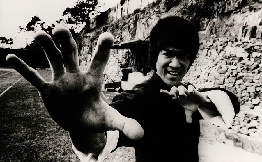 Bruce Lee with his hands up in a pose in a scene from the film Enter the Dragon