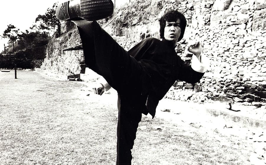 Bruce Lee with his foot kicking high