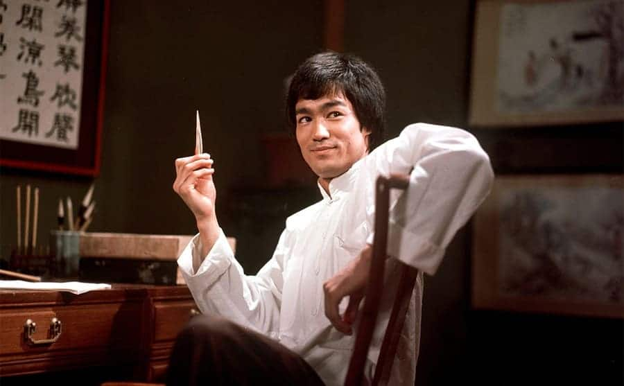 Bruce Lee holding something sharp in his hand while sitting at a desk in a scene from Enter the Dragon