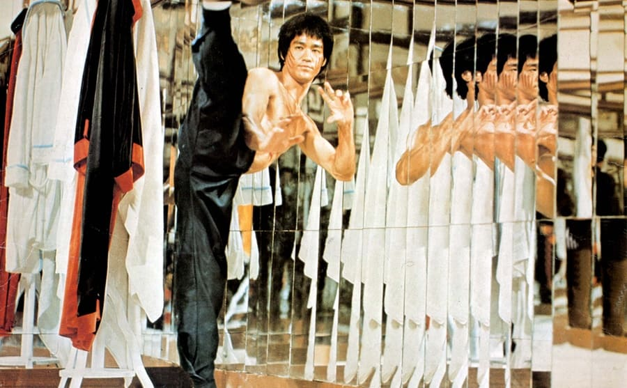 Bruce Lee with his leg kicked upward and his reflection in the multiple mirrors next to him