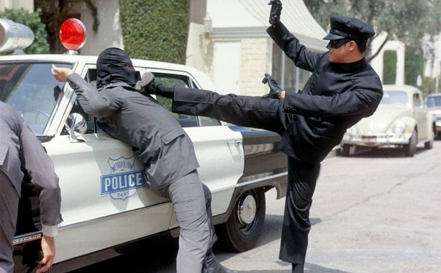 Bruce Lee pinning a bad guy up to he police car using his foot in a scene from The Green Hornet