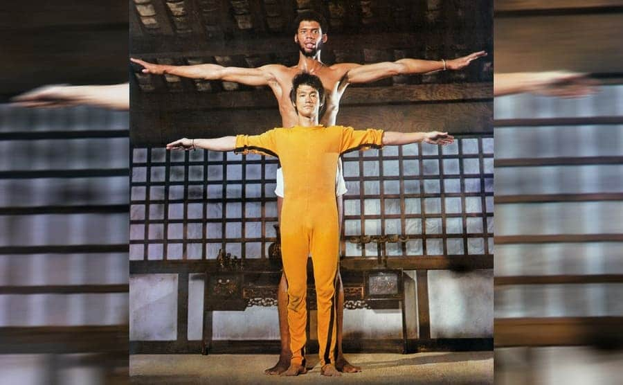 Bruce Lee and Kareem Abdul Jabbar with their arms out standing next to each other