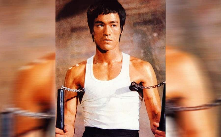 Bruce Lee holding two sets of nunchucks in the film Enter the Dragon