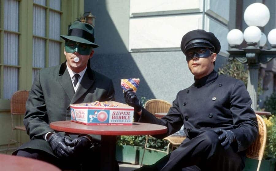 Van Williams and Bruce Lee sitting at a table chewing bubble gum and people watching in the show The Green Hornet