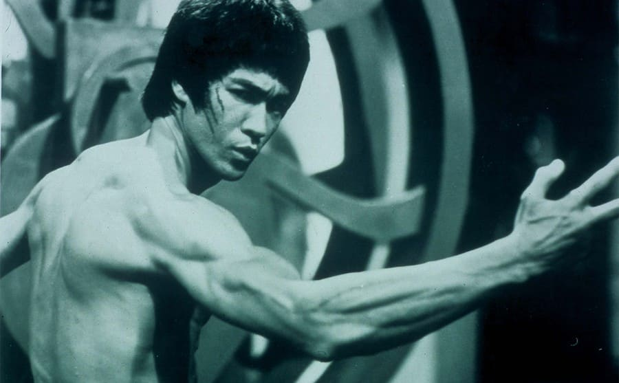 Bruce Lee flexing his muscles in a scene from Enter the Dragon