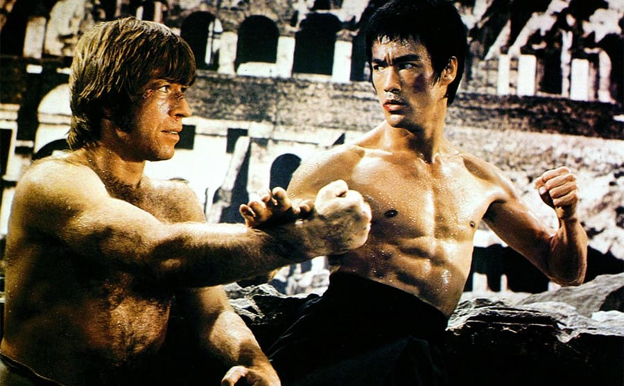 Bruce Lee blocking a punch from Chuck Norris and raising his other hand in a fist