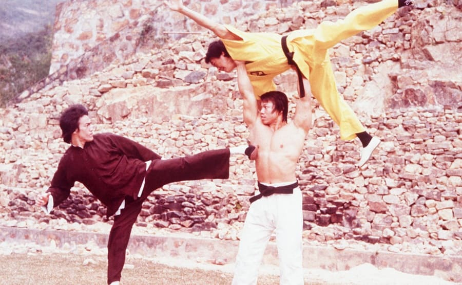 Bruce Lee doing a fight scene with two men, one who is holding the second man above his head while Bruce delivers a kick to the ribs