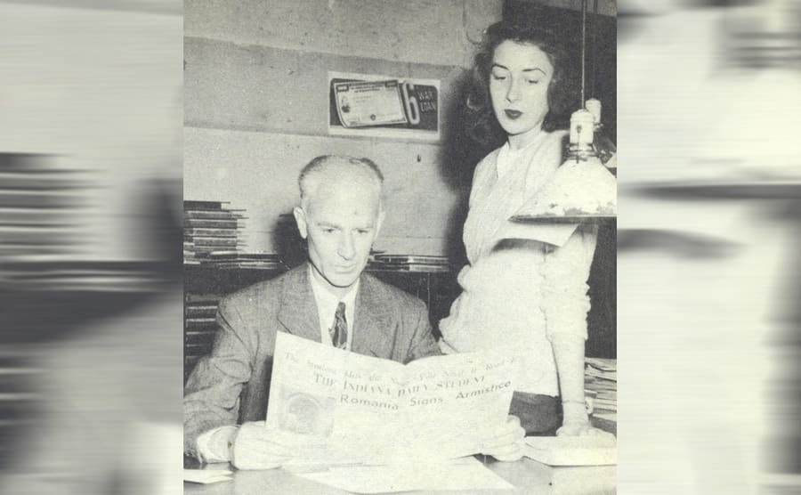 Ernie Pyle reading a newspaper while his girlfriends looks over his shoulder