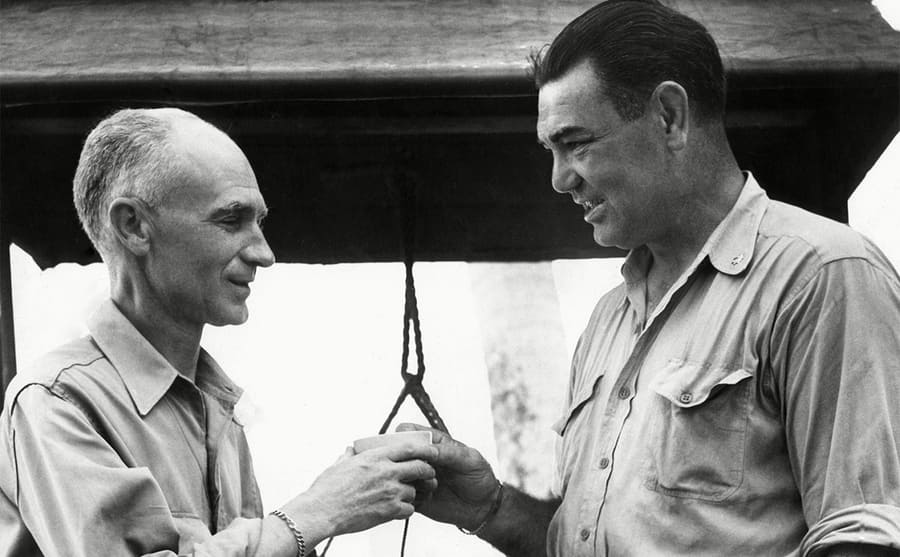 Ernie Pyle handing Jack Dempsey a cup of coffee