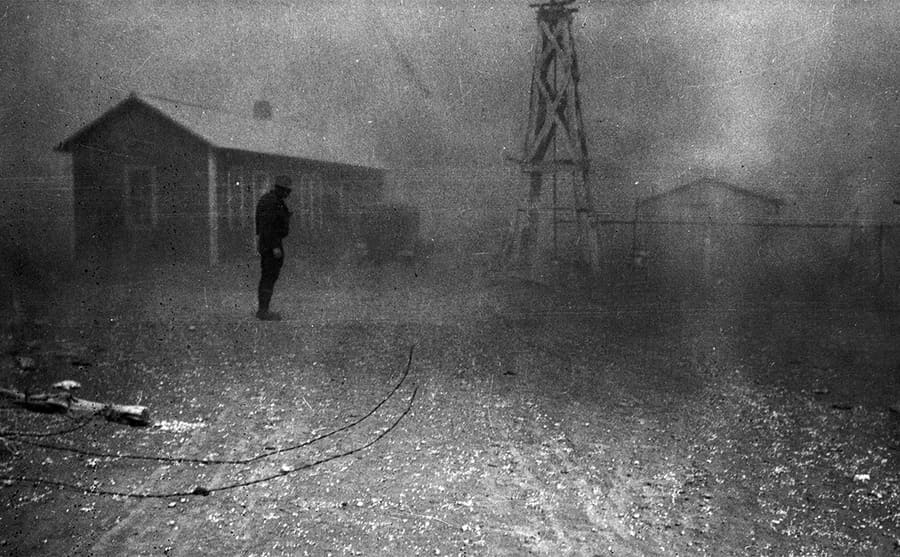 A photograph of a farmer with houses behind him and dust creating a cloudy effect