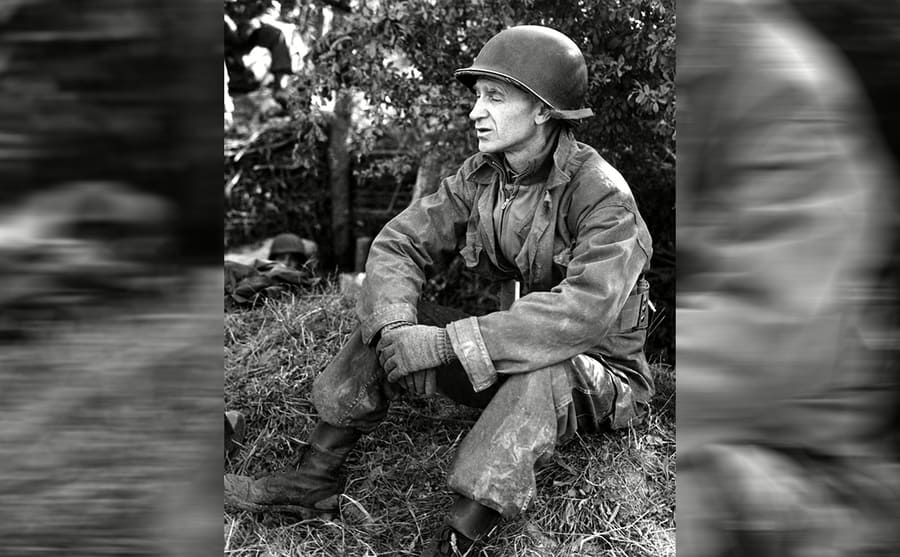 Ernie Pyle sitting on a small grassy hill in uniform and a helmet