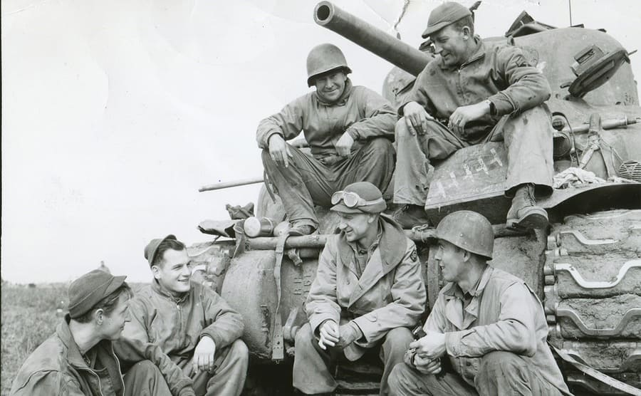 Ernie Pyle sitting in front of a tank with soldiers