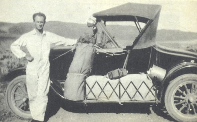Ernie Pyle standing next to his car