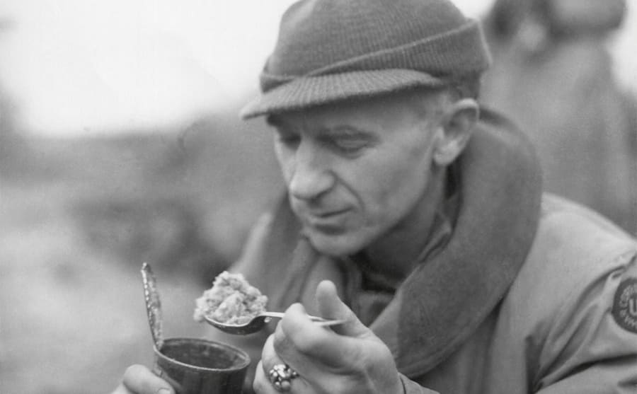 Ernie Pyle eating out of a can