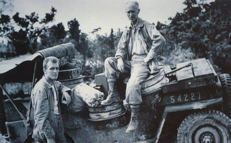 Ernie Pyle sitting on the back of a Jeep