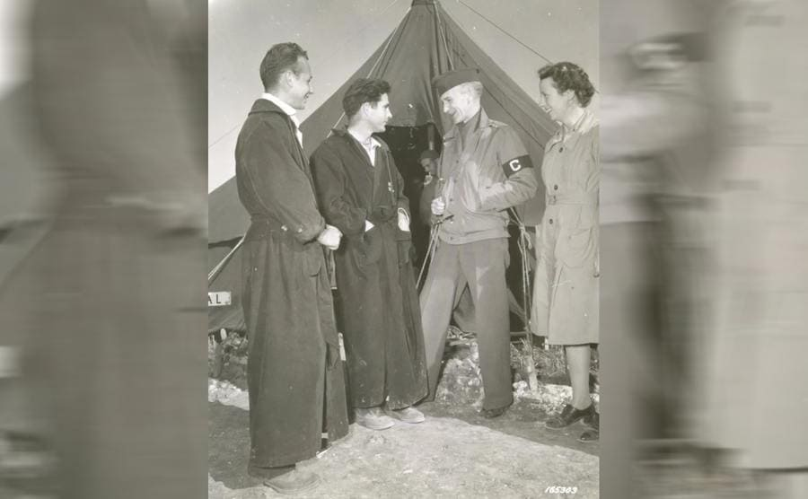 Ernie Pyle with his wife speaking to soldiers in front of a tent