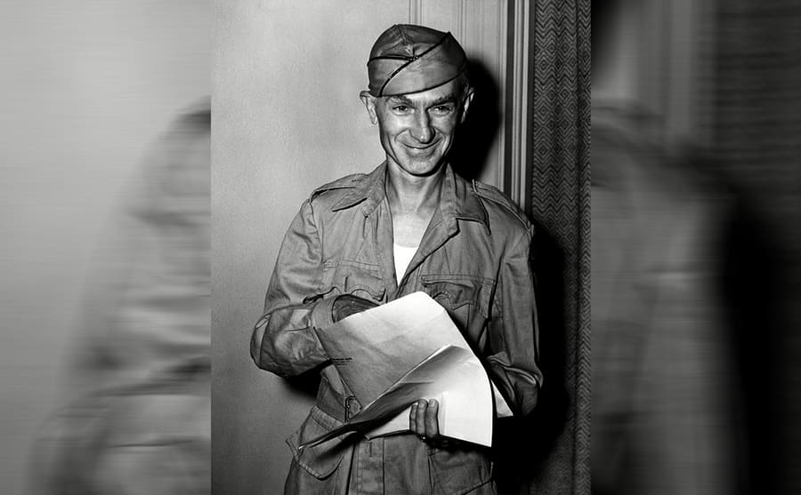Ernie Pyle reaching into a large envelope that he is holding