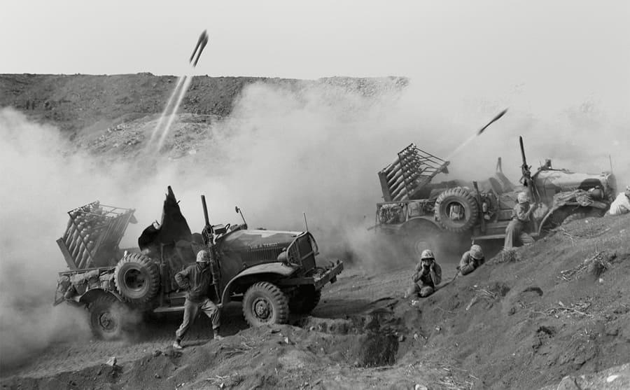 Two military tracks launching rockets