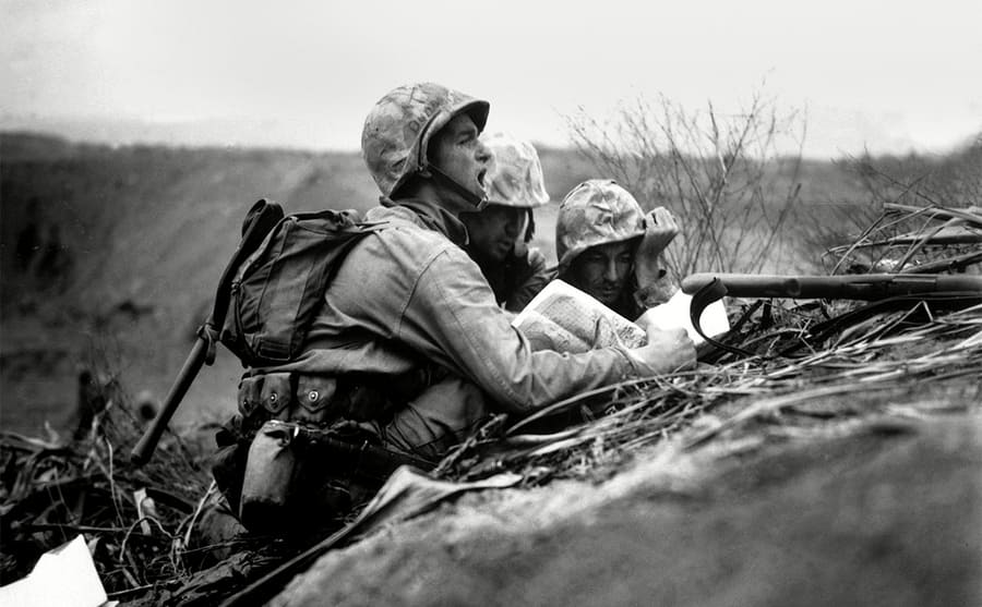Few soldiers looking at a map behind a hill