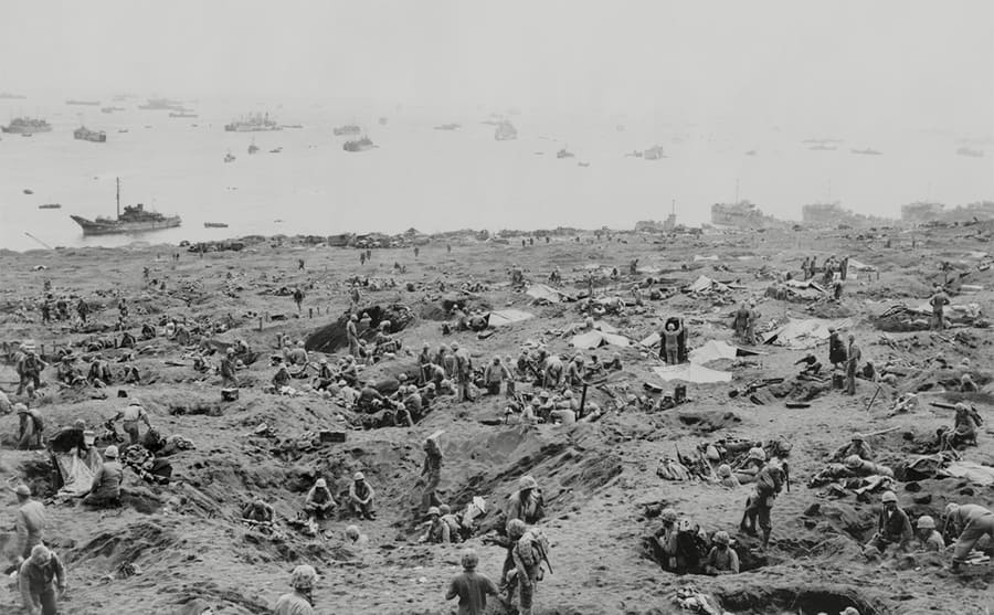 Soldiers in foxholes and landing crafts are beached on right