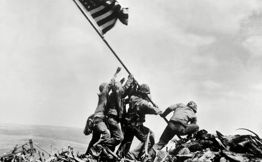 Soldiers raising the US flag over a hill