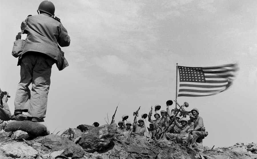 Soldiers sitting on a hill holding the US flag and cheering towards a photographer